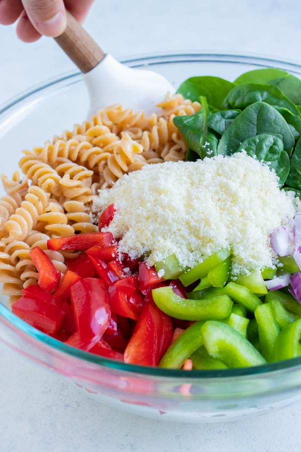 Chopped veggies, spinach, and Parmesan cheese are added to the bowl of noodles.