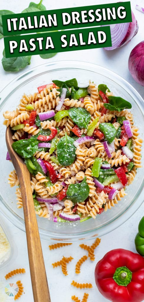 A big bowl of Italian dressing pasta salad is set on the counter next to fresh peppers and onions.