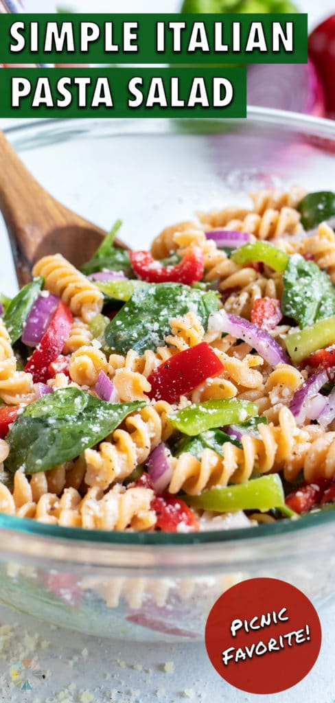 A bowl of Italian pasta salad is served with a wooden spoon for a side.
