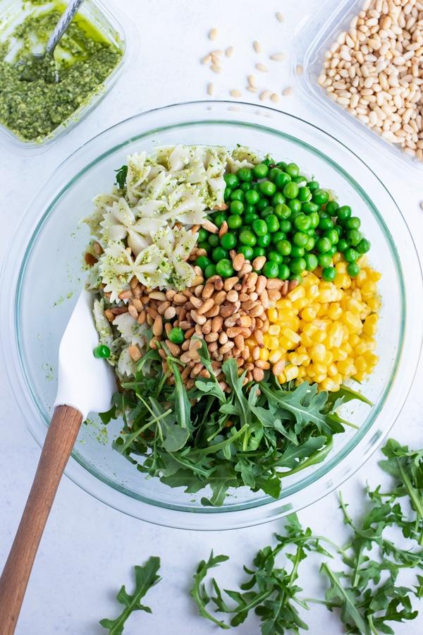 Pesto pasta, peas, corn, arugula, pine nuts are all added to the bowl.