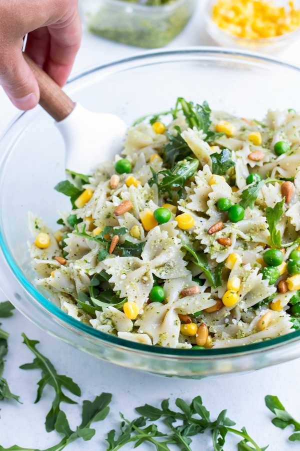 Pesto pasta salad is mixed in a glass bowl with a rubber spatula.