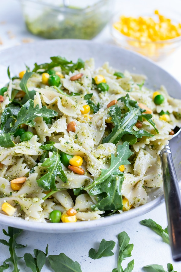 A bowl of pesto pasta salad is served for a healthy side dish.