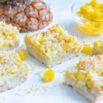 Pina colada bars are set on the counter near fresh pineapple.