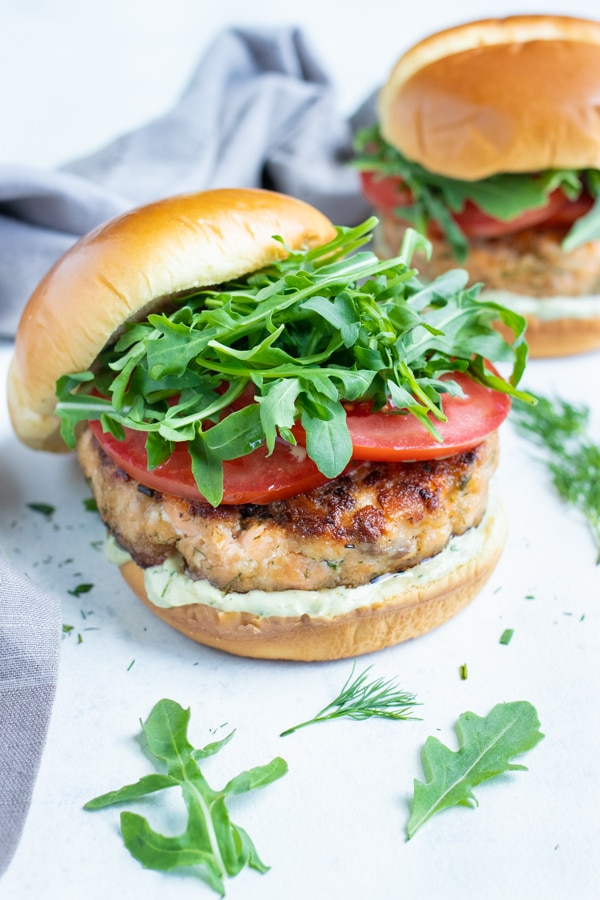 The top bun of the salmon burger is tilted off the salmon burger.