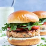 Two salmon burgers are served for a seafood dinner.