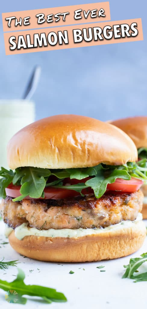 Salmon burger with lettuce, tomato, and avocado ranch is set on the counter.
