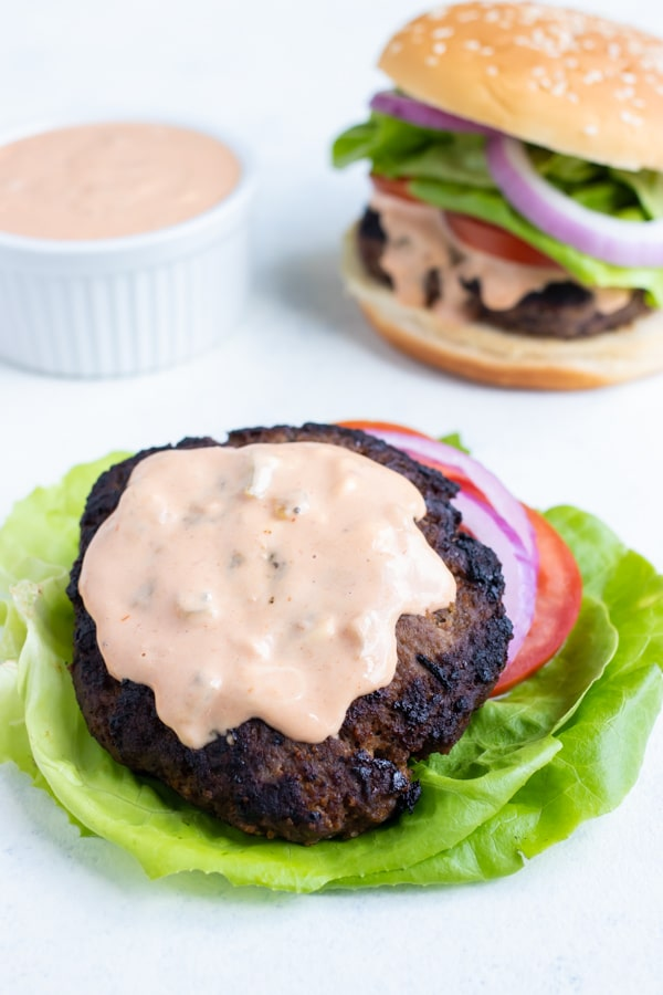 This copycat Big Mac sauce is spread on a lettuce-wrapped burger.