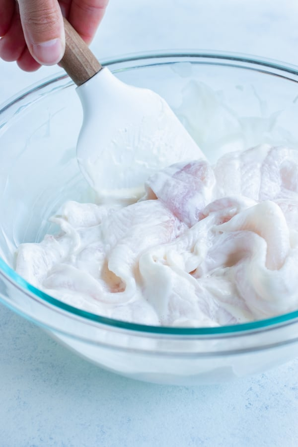 The fish is coated in mayonnaise in a glass bowl.