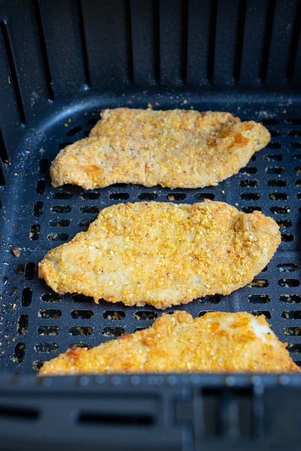 Three fish fillets are shown in the air fryer.