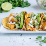 Air fryer tacos are filled with lime crema, avocado, and taco slaw.