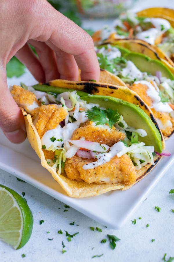 A hand is used to lift the taco from the plate.