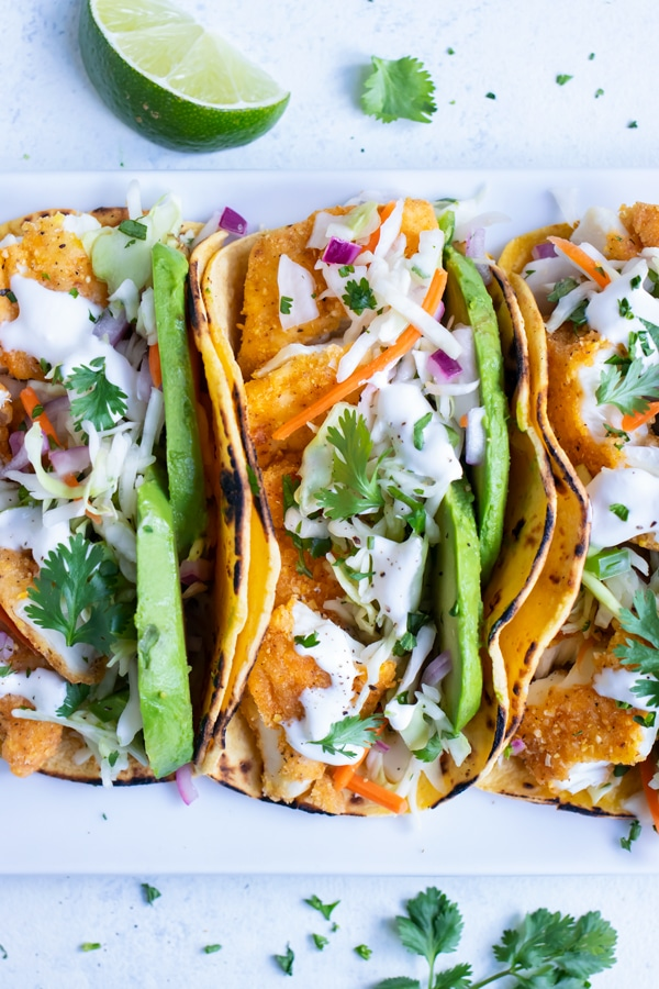Tacos are set side by side on a plate for a meal.