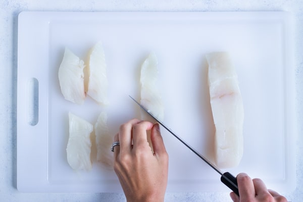 A knife is used to prepare the fish fillets.