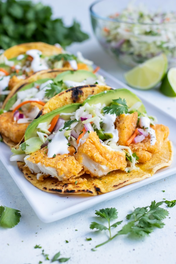 A plate with multiple fish tacos are shown