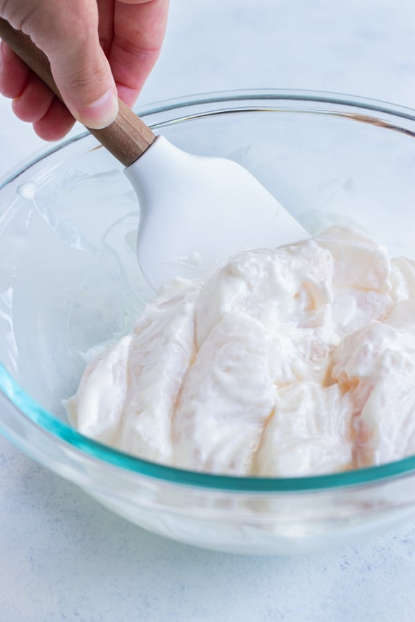 The fish fillets are covered in mayonnaise in a bowl.