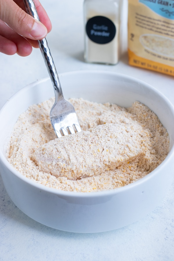 The raw fish is covered in the cornmeal flour mixture.