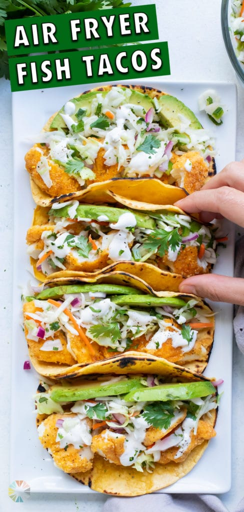 Crispy air fryer fish tacos are picked up by a hand.