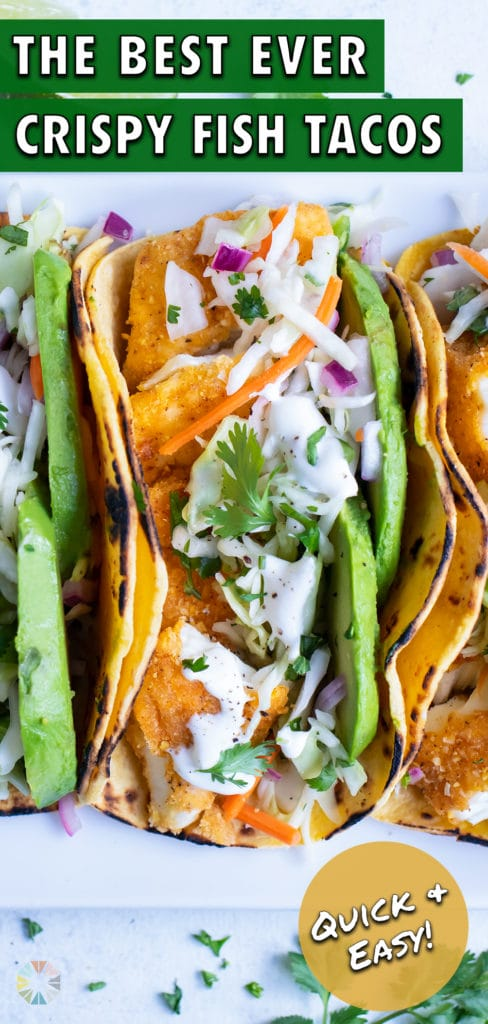 Three fish tacos are served side by side on a white plate for dinner.