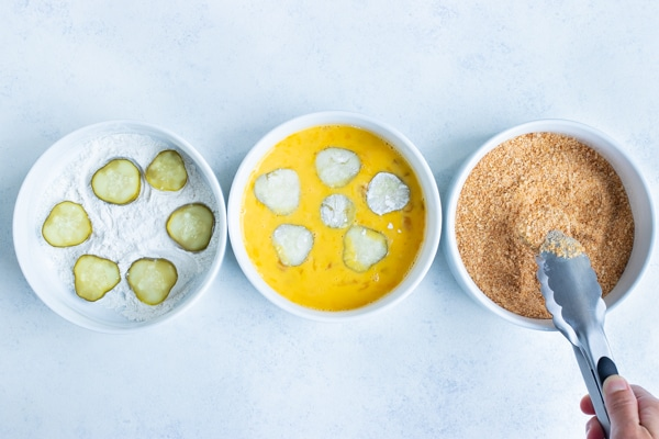 The pickles are coated in flour, egg mixture, and bread crumbs.
