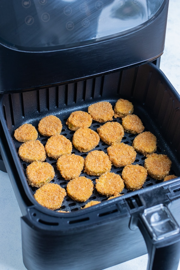 The coated pickles are laid in a single layer in the air fryer.