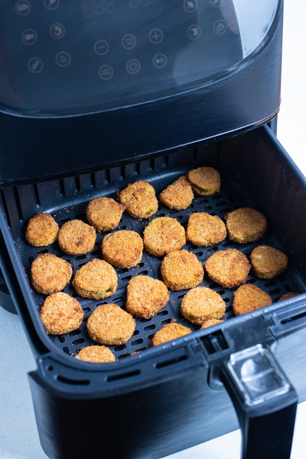 The crispy pickles are cooked in the air fryer until golden brown.