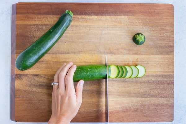 Zucchini is cut into slices on a cutting board. for this healthy recipe.