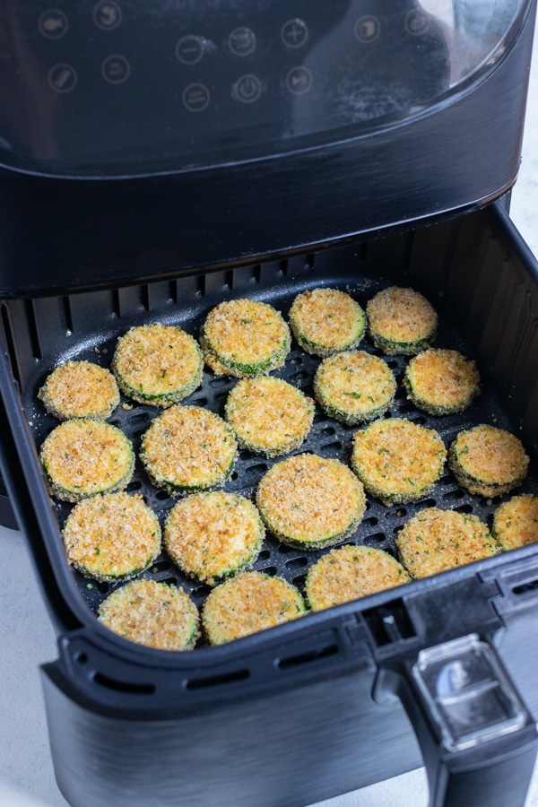 The covered zucchini chips are laid in a flat layer in the air fryer.