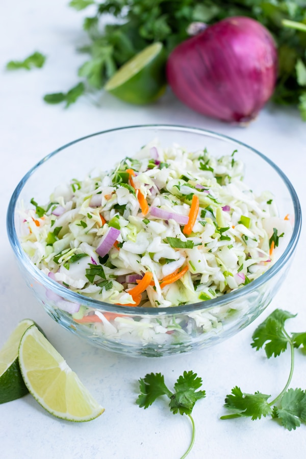 Low-carb taco slaw is served from a glass bowl on the counter.