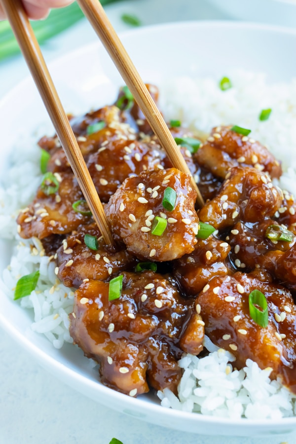 General Tsos Chicken is eaten with chopsticks and white rice.