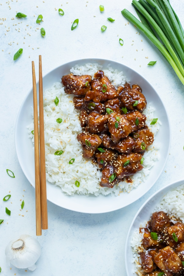 A plate is used to serve homemade General Tao Chicken with white rice.