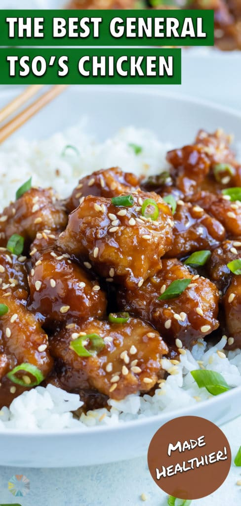 Sweet and spicy chicken is served with rice and chopsticks on a white plate.