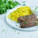 Lamb Kofta Kebabs are served on a plate with yellow rice.
