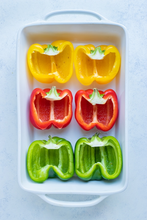 The bell peppers are lined in a baking dish before filling.