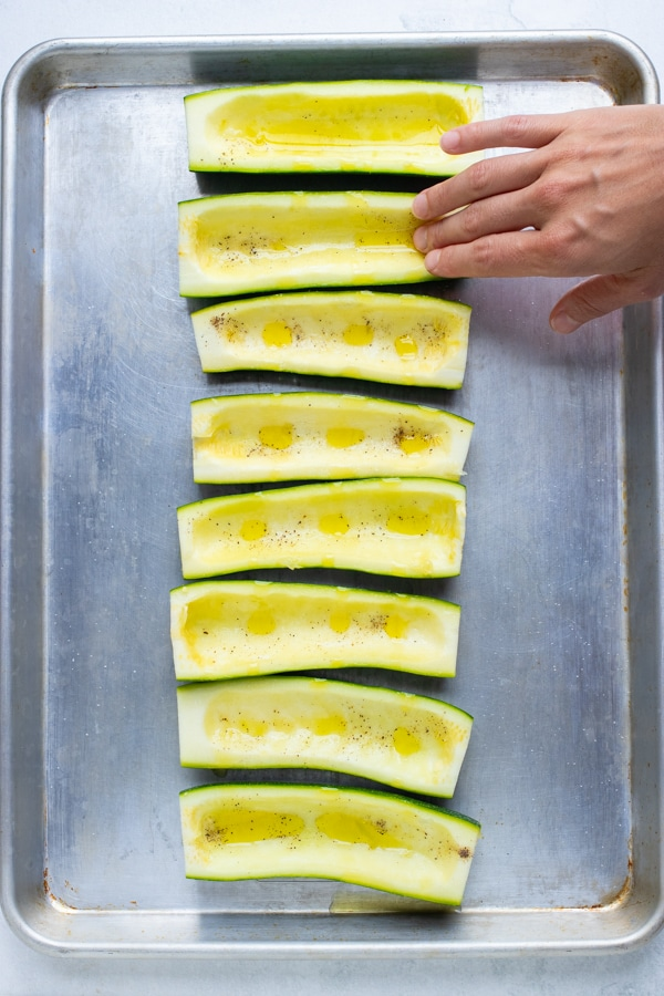 Oil being rubbed on zucchini boats before being baked in the oven.