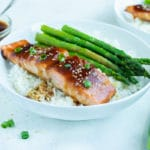 A white plate is used to serve the teriyaki salmon, rice, and asparagus.