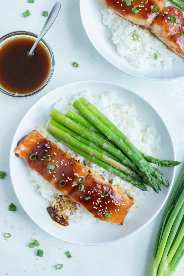 White rice, asparagus, and teriyaki salmon are served for a healthy dinner.