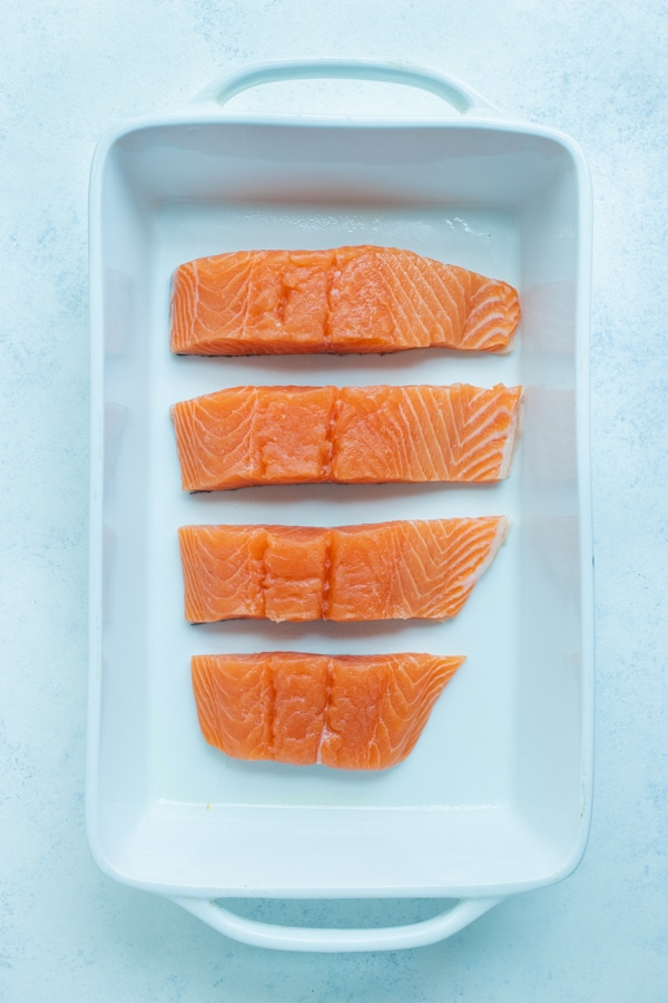 The four pieces of salmon are placed in a baking dish.
