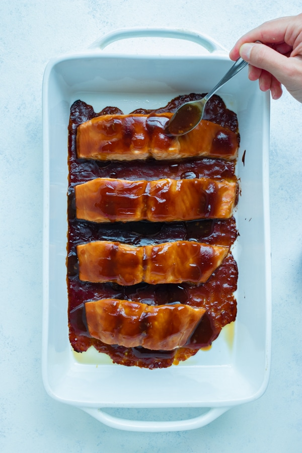 Teriyaki sauce is added to the salmon filets before being baked in the oven.