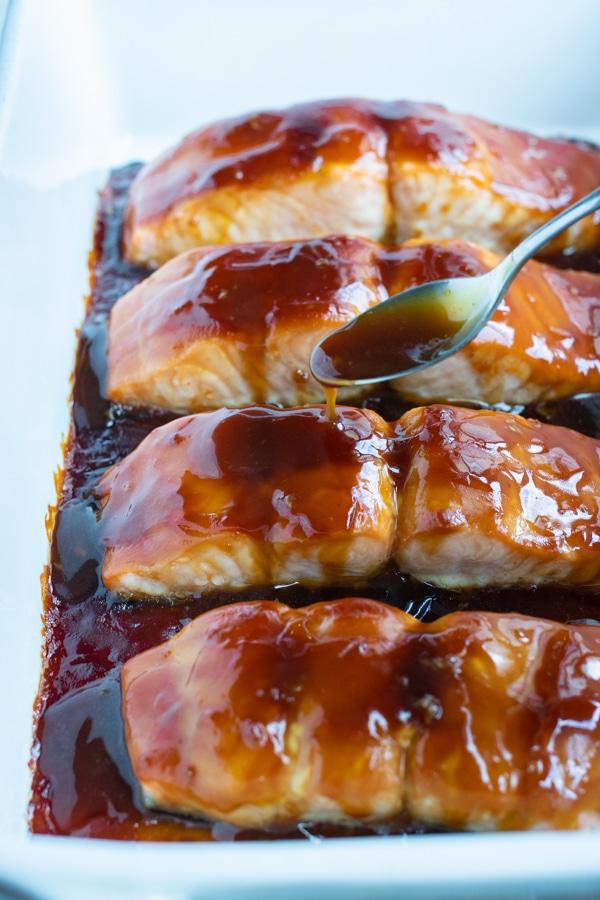 Teriyaki sauce is spooned onto the salmon.