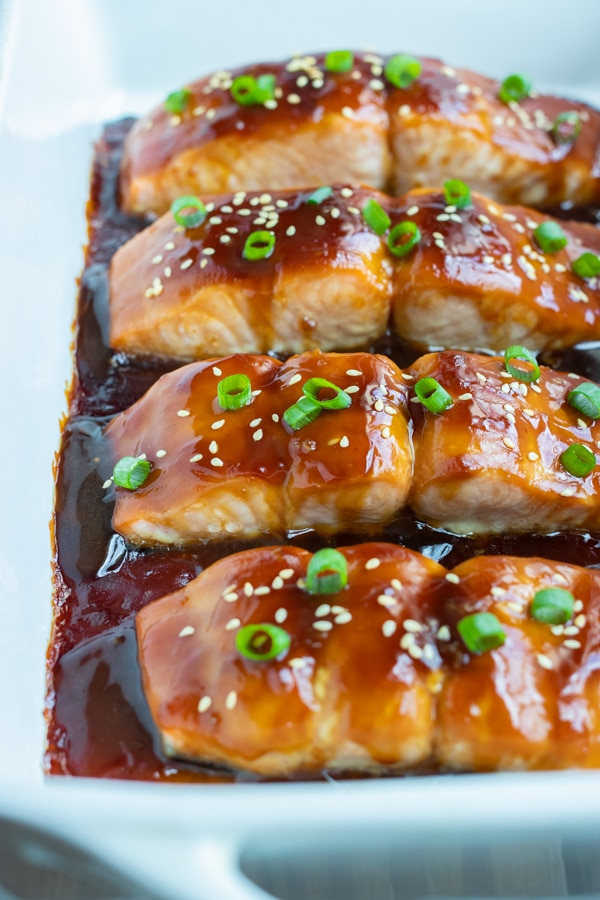 Healthy teriyaki salmon is served from a white baking dish.