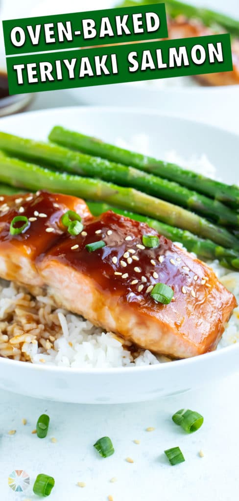 Teriyaki salmon is served on top of fluffy white rice.