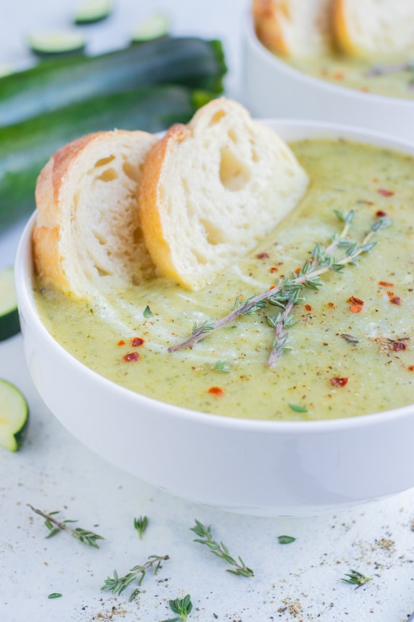 Creamy zucchini soup is served with bread in a bowl.