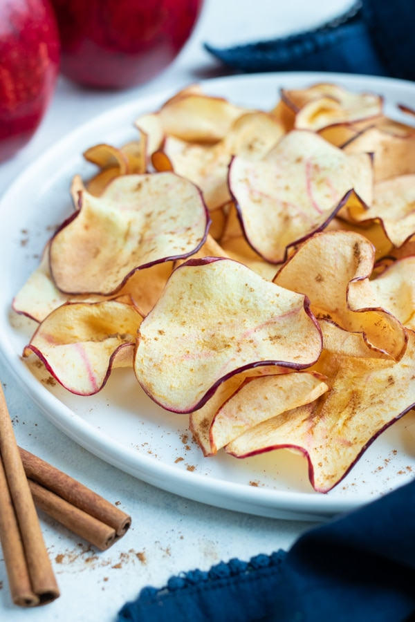 Crispy and healthy apple chips are topped with cinnamon.