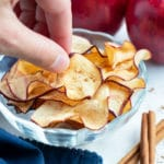 An apple chip is picked up by a hand for a snack.
