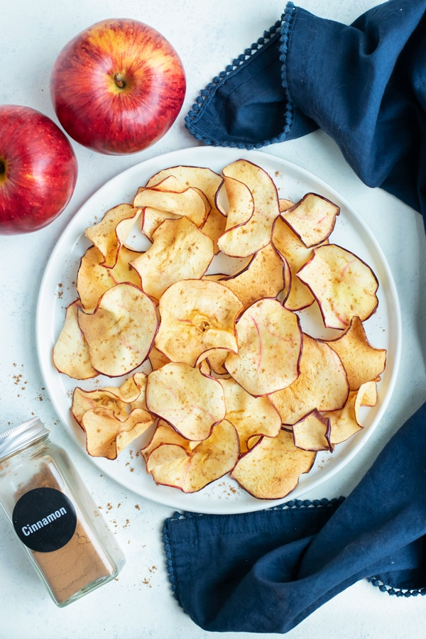 A full plate of air fryer apple chips is shown on the counter next to raw apples.