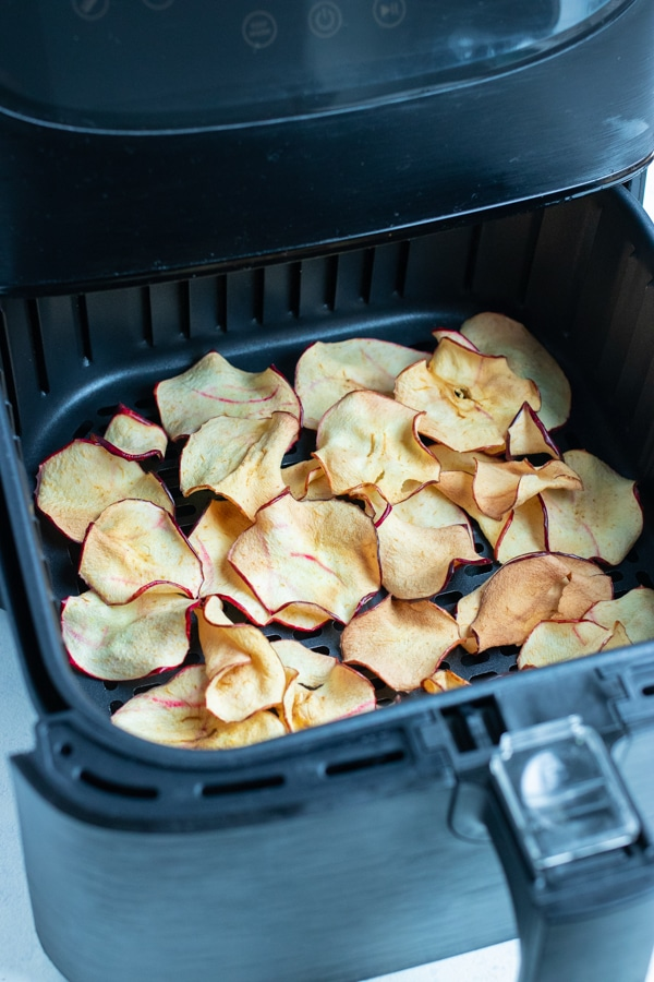 Apple slices are cooked in the air fryer until crispy.