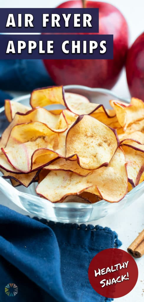 A bowl of apple chips is set next to sticks of cinnamon.