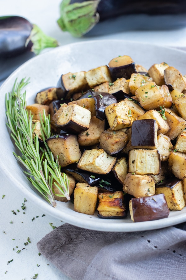 Eggplant is served with fresh herbs from a white bowl.