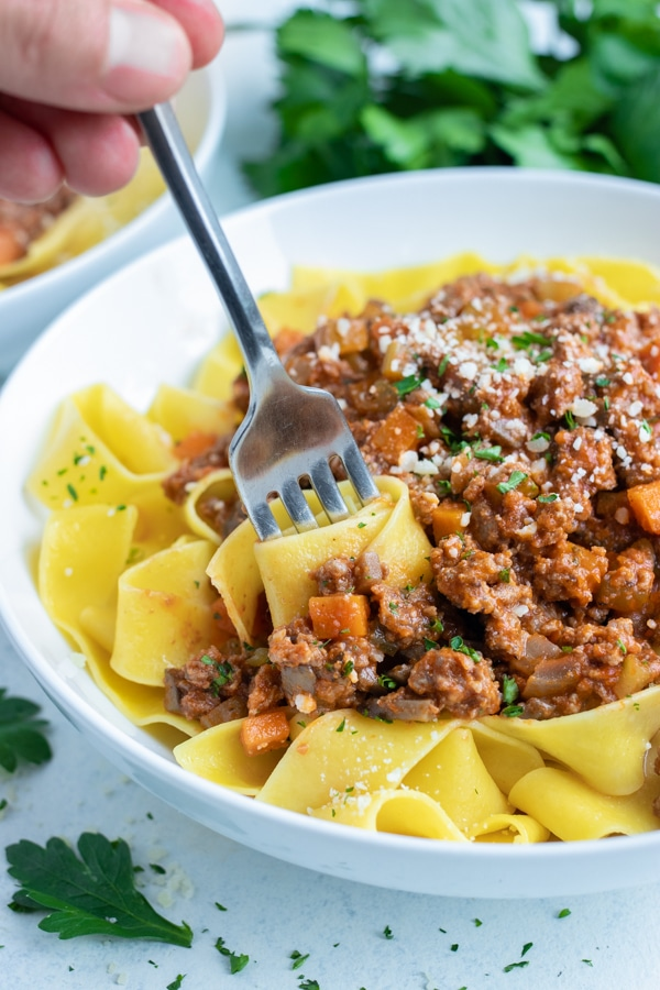 A bowl of authentic bolognese sauce and noodles is shown on the counter.