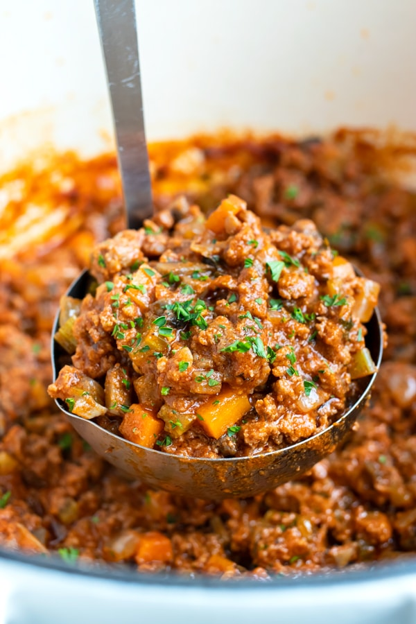 Authentic, gluten-free beef bolognese sauce is shown In a bowl with a ladle.